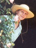 Photograph of Eva Cassidy wearing a hat, peeking out from behind a rosebush